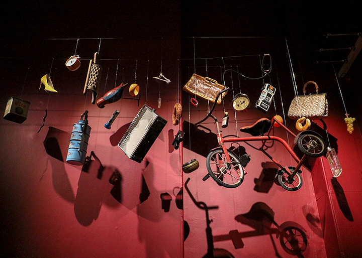 miscellaneous household objects suspended in front of a dark red wall with dramatic lighting